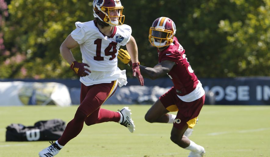 Washington Redskins wide receiver Trey Quinn (14) looks for the pass as cornerback Greg Stroman (37) defends during the first day of NFL football training camp in Richmond, Va., Thursday, July 25, 2019. (AP Photo/Steve Helber)