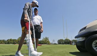 Injured Washington Redskins quarterback Alex Smith, left, walks to a cart as he talks with former quarterback Joe Theisman, right, as he leaves the practice field during the first day of NFL football training camp in Richmond, Va., Thursday, July 25, 2019. (AP Photo/Steve Helber)