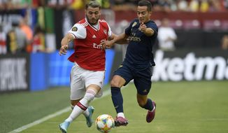 Real Madrid forward Lucas Vazquez, right, battles for the ball against Arsenal defender Sead Kolasinac, left, during the first half of an International Champions Cup soccer match, Tuesday, July 23, 2019, in Landover, Md. (AP Photo/Nick Wass)