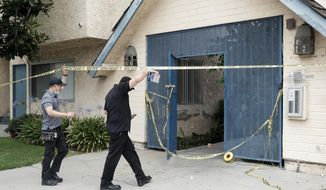 Investigators walk into an apartment where a shooting occurred in the Canoga Park area of Los Angeles on Thursday, July 25, 2019.  Police say a gunman shot five people, killing three, in two attacks in Los Angeles before he tried to rob someone outside a bank. (Dean Musgrove/The Orange County Register via AP)