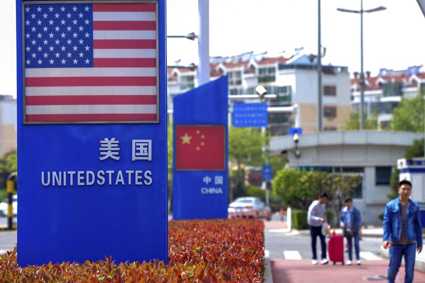 In this May 8, 2019, photo, people walk by a display boards featuring the U.S. and Chinese flags in a special trade zone in Qingdao in eastern China's Shandong province. A government spokesman says Chinese companies have expressed willingness to import U.S. farm goods as envoys prepare to meet next week for talks aimed at ending a tariff war. (Chinatopix via AP)
