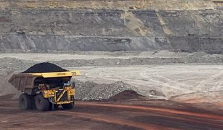 FILE - In this March 28, 2017, file photo, a dump truck hauls coal at Contura Energy's Eagle Butte Mine near Gillette, Wyo.Two coal mines in Wyoming and one in West Virginia owned by a company in bankruptcy could reopen if a judge approves a purchase offer. Court documents show Bristol, Tennessee-based Contura Energy has offered $20.6 million for the mines owned by Milton, West Viginia-based Blackjewel LLC. The mines have been closed since Blackjewel filed for bankruptcy July 1, 2019. (AP Photo/Mead Gruver, File)