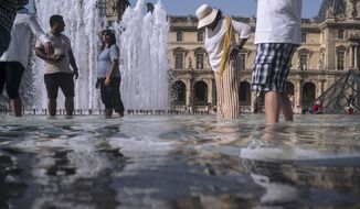 People cool off next to the fountains at Louvre Museum in Paris, France, Wednesday, July 24, 2019. Temperatures in Paris are forecast to reach 41 degrees C (86 F), on Thursday. (AP Photo/Rafael Yaghobzadeh)
