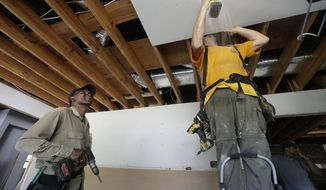 In this Tuesday, July 2, 2019, photo, homeowner Clifton Hall, left, watches and helps volunteer Tom Poston, with Baptists On Mission, make repairs to Hall's home which was damaged by Hurricane Florence the year before, in Spring Lake, N.C. North Carolina hurricane survivors are frustrated with the slow spending of federal long-term housing recovery funds. (AP Photo/Gerry Broome)