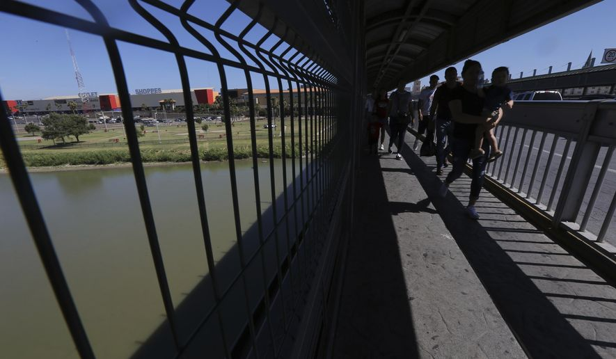 In this July 18, 2019, photo, people walk back to Mexico on International Bridge 1 Las Americas, a legal port of entry that connects Laredo, Texas in the U.S. with Nuevo Laredo, Mexico. (AP Photo/Marco Ugarte) **FILE**