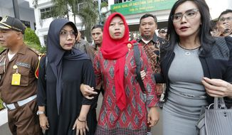 FILE - In this July 12, 2019, file photo, Baiq Nuril Maknun, center, arrives at the Attorney General's office in Jakarta, Indonesia. The woman sentenced to prison for recording her boss's sexual harassment wept and lawmakers clapped as Indonesia's parliament unanimously approved an amnesty recommended by the country's president. (AP Photo/Tatan Syuflana, File)