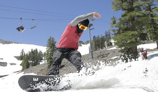 "FILE - In this July 1, 2017 file photo, a snowboarder cuts throughout the snow at the Squaw Valley Ski Resort in Squaw Valley, Calif. A proposal to link a pair of Lake Tahoe ski resorts with a 2-mile-long gondola is moving closer to final approval. Squaw Valley President Ron Cohen says Placer County's approval of the project on Tuesday, July 23, 2019, is one of the ""last crucial steps"" toward linking Squaw Valley and Alpine Meadows. (AP Photo/Rich Pedroncelli, File)"