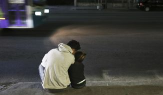 In this July 18, 2019, file photo, a migrant father and daughter sit on the sidewalk after getting off a bus that brought them all the way from Nuevo Laredo to Monterrey, Mexico. The group was placed on the bus by Mexican migration authorities, arriving in this northern Mexican city late at night and left them to fend for themselves with no support on housing, work or schooling for children, who appear to make up about half the group. (AP Photo/Marco Ugarte)