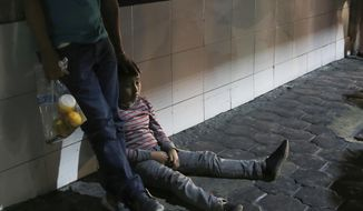 In this July 18, 2019, file photo, a migrant child and his father stay together after being bused by Mexican migration authorities from Nuevo Laredo to Monterrey, Mexico. Unlike asylum seekers who wait in line, often for months, to file claims in the U.S. and then return to the Mexican border cities where they were before, all those taken to Monterrey who spoke with AP said they had crossed illegally and spent several days in U.S. detention centers before being returned with a court date. (AP Photo/Marco Ugarte)