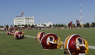 Helmets are lined up along the practice field as players begin drills during the first day of the Washington Redskins NFL football training camp in Richmond, Va., Thursday, July 25, 2019. (AP Photo/Steve Helber) ** FILE **