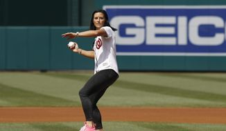 Ali Krieger, a member of the United States women's national soccer team, throws out a ceremonial first pitch before a baseball game between the Colorado Rockies and the Washington Nationals, Thursday, July 25, 2019, in Washington. (AP Photo/Patrick Semansky)