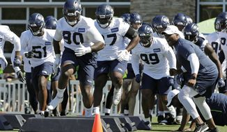 Seattle Seahawks defensive tackle Jarran Reed (90) runs a drill with teammates during NFL football training camp, Thursday, July 25, 2019, in Renton, Wash. (AP Photo/Ted S. Warren)