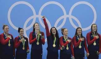 FILE - In this Aug. 19, 2016, file photo, members of the United States women's water polo team celebrate with their gold medals on the podium after winning their gold medal match against Italy at the 2016 Summer Olympics in Rio de Janeiro, Brazil. For decades, the question at the Summer Olympics hasn't been whether the United States will top the medals table, but by how much.If anyone on U.S. soil has a problem with that _ and given the headlines of the last few years, plenty of people do _ well, imagine the alternative. (AP Photo/Eduardo Verdugo, File)