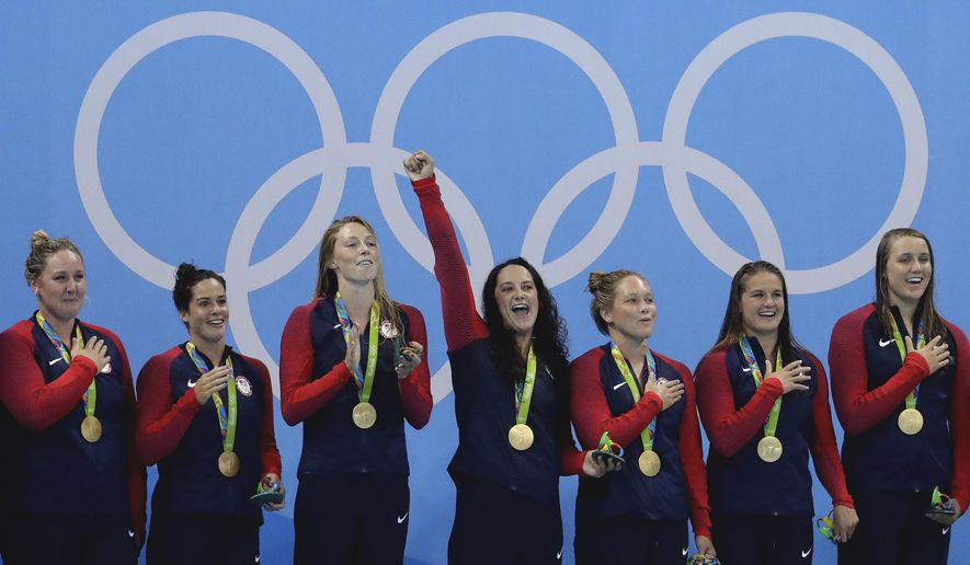 In this Aug. 19, 2016, file photo, members of the United States women's water polo team celebrate with their gold medals on the podium after winning their gold medal match against Italy at the 2016 Summer Olympics in Rio de Janeiro, Brazil. (AP Photo/Eduardo Verdugo, File)