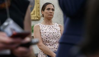White House press secretary Stephanie Grisham, listens as President Donald Trump speaks with reporters on the South Lawn of the White House before departing, Wednesday, July 17, 2019, in Washington. (AP Photo/Alex Brandon)