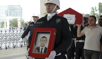A police honour guard carry the coffin of Osman Kose, a 38-year-old Turkish diplomat killed in Iraq, before his funeral prayers in Ankara, Turkey, Thursday, July 18, 2019. A gunman opened fire inside a restaurant in the northern Iraqi city of Irbil on Wednesday, killing a Turkish diplomat working at Ankara's consulate, Turkey's state-run news agency and Iraqi media said.(AP Photo/Burhan Ozbilici)