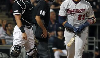 Minnesota Twins' Nelson Cruz watches his two run home run during the fifth inning of a baseball game as Chicago White Sox catcher James McCann (33) and home plate umpire Ed Hickox (15) look on Thursday, July 25, 2019, in Chicago. It was Cruz's third home run of the game. (AP Photo/Jeff Haynes)