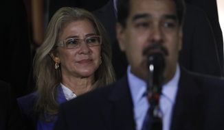 FILE - In this June 21, 2019 file photo, first lady Cilia Flores stands behind her husband Venezuela's President Nicolas Maduro during a press conference, at Miraflores Presidential Palace, in Caracas, Venezuela. The U.S. on Thursday, July 25, 2019, placed sanctions on two businessman and three sons of Venezuela's first lady, for allegedly forming part of a network that stole hundreds of millions in dollars from food import contracts at a time of widespread hunger in the crisis-wracked South American nation. (AP Photo/Ariana Cubillos, File)