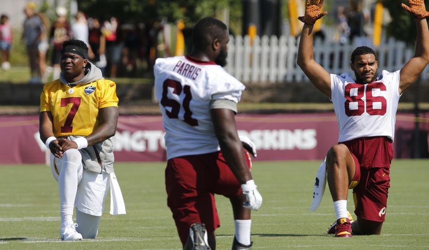 Washington Redskins quarterback Dwayne Haskins Jr. (7), offensive tackle Timon Parris (61), and tight end Jordan Reed (86) stretch during the first day of NFL football training camp in Richmond, Va., Thursday, July 25, 2019. (AP Photo/Steve Helber)