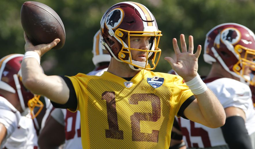 Washington Redskins quarterback Colt McCoy (12) tosses a pass during the NFL football training camp in Richmond, Va., Friday, July 26, 2019. (AP Photo/Steve Helber)