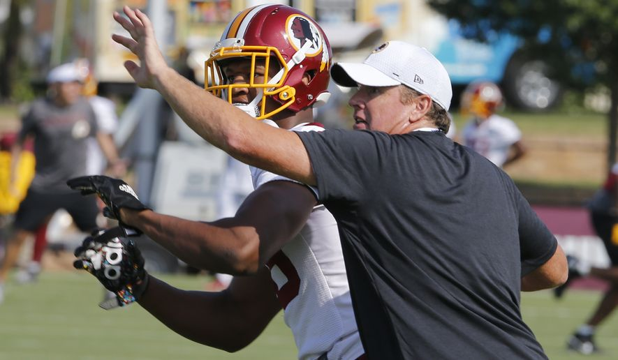 Washington Redskins tight end Donald Parham Jr., tries to catch a pass as head coach Jay Gruden tries to break it up during NFL football training camp in Richmond, Va., Friday, July 26, 2019. (AP Photo/Steve Helber)