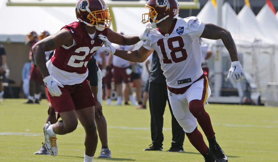 Washington Redskins wide receiver Josh Doctson (18) runs a route in front of cornerback Quinton Dunbar (23) during the NFL football training camp in Richmond, Va., Friday, July 26, 2019. (AP Photo/Steve Helber) ** FILE **