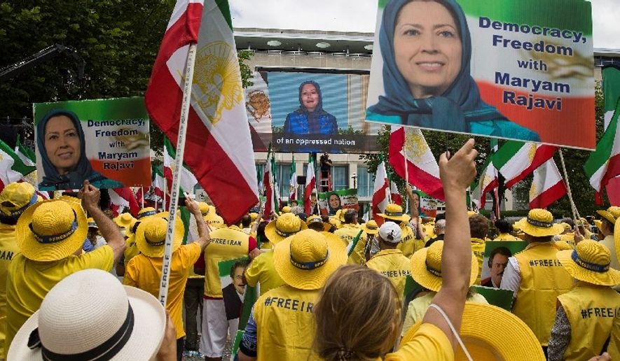 Activists gather at the State Department and watch a message on the screen from Maryam Rajavi before a march to the White House to call for regime change in Iran, Friday, June 21, 2019, in Washington. (AP Photo/Alex Brandon)