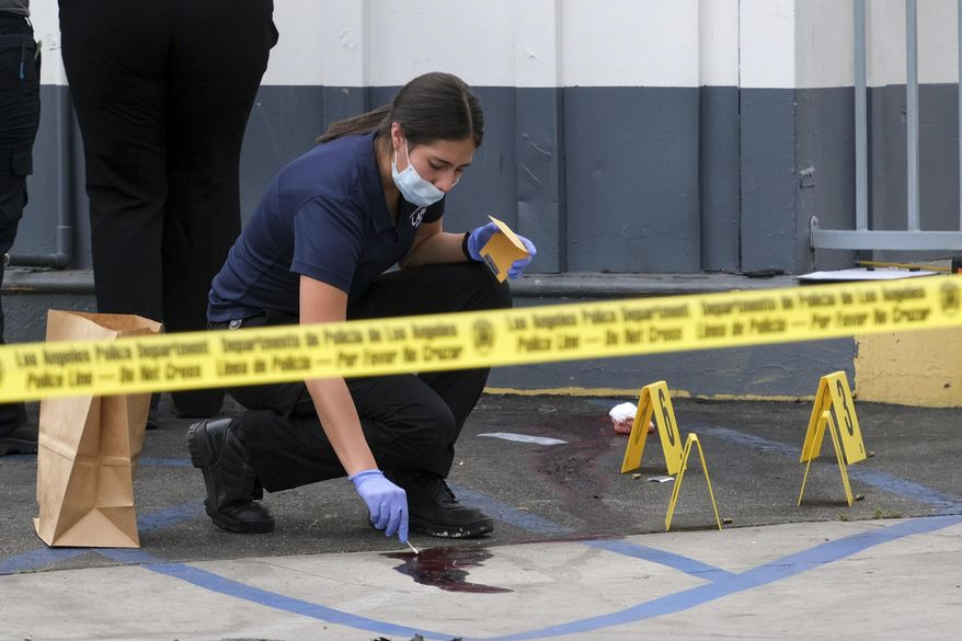 Los Angeles Police Department crime investigators collect evidence at one of the scenes of a triple shooting, a Shell gas station in the North Hollywood section of Los Angeles, Thursday, July 25, 2019. (David Crane/The Orange County Register via AP)