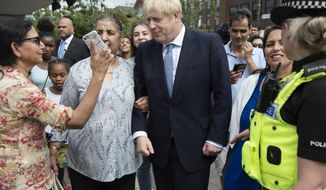 Britain's Prime Minister Boris Johnson on a walkabout during a visit to North Road, Birmingham, England, Friday, July 26, 2019. Johnson is making a plethora of promises that go well beyond Brexit: boosting police numbers, increasing school spending, improving internet speeds, even building electric planes. Johnson has not given details of where the money would come from to pay for these plans, though he has threatened to withhold a payment of 39 billion pounds ($49 billion) as part of a Brexit divorce bill that May agreed to if there is no deal. (Geoff Pugh/Pool Photo via AP)