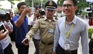 Former Radio Free Asia reporter Yeang Sothearin, left, arrives at the Phnom Penh Municipal Court, in Phnom Penh, Cambodia, Friday, July 26, 2019. The espionage trial of two Cambodian journalists, including Yeang Sothearin, who formerly worked for a U.S. government-funded radio station has begun almost two years after their arrests. (AP Photo/Heng Phearum)
