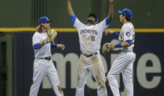 Milwaukee Brewers' Ben Gamel, Lorenzo Cain and Christian Yelich celebrate after a baseball game against the Chicago Cubs Friday, July 26, 2019, in Milwaukee. The brewers won 3-2. (AP Photo/Morry Gash)