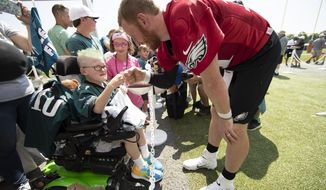 Philadelphia Eagles quarterback Carson Wentz bumps fists with eleven-year-old Giovanni Hamilton who is attending the practice as part of a wish granted by Bianca's Kids at the NFL football team's training camp in Philadelphia, Friday, July 26, 2019. (AP Photo/Matt Rourke)