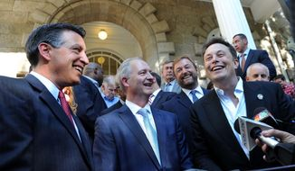 FILE - In this Sept. 4, 2014, file photo, Nevada Gov. Brian Sandoval, left, Steve Hill, executive director of the governor's office of Economic Development, and Elon Musk, Chairman and CEO of Tesla, laugh while answering reporters' questions on the steps of the capitol building in Carson City, Nev., after a press conference announcing that Nevada had been selected as the site for the Tesla Battery Gigafactory. Sen. Dean Heller, R-Nev., is behind Hill and Musk. Nearly two-thirds of companies granted tax breaks by a government office empowered in 2011 to attract businesses, jobs and investment to Nevada have failed to meet at least one application benchmark. (Tim Dunn/The Reno Gazette-Journal via AP, File)