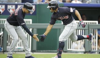 Cleveland Indians' Francisco Lindor celebrates with third base coach Mike Sarbaugh after hitting a solo home run during the first inning of a baseball game against the Kansas City Royals Thursday, July 25, 2019, in Kansas City, Mo. (AP Photo/Charlie Riedel)