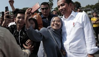 A Muslim woman takes a selfie with Indonesian President Joko Widodo, right, during his visit at the Old Town in Jakarta, Indonesia, Friday, July 26, 2019. Indonesian President Joko Widodo said in an interview Friday that he will push ahead with sweeping and potentially unpopular economic reforms, including a more business-friendly labor law, in his final term because he is no longer constrained by politics. (AP Photo/Dita Alangkara)