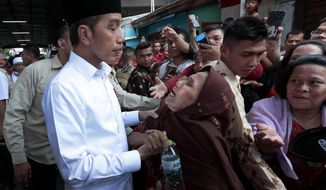 Indonesian President Joko Widodo, left, listens to an elderly woman during his visit to Tanah Tinggi, a lower-income neighborhood, in Jakarta, Indonesia, Friday, July 26, 2019. Indonesian President Joko Widodo said in an interview Friday that he will push ahead with sweeping and potentially unpopular economic reforms, including a more business-friendly labor law, in his final term because he is no longer constrained by politics. (AP Photo/Dita Alangkara)