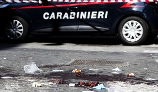 A car of the Italian Carabinieri, paramilitary police, is parked near a blood stain, the site where Carabiniere Vice Brigadier Mario Cerciello Rega was stabbed to death by a thief in Rome, Friday, July 26, 2019. Cerciello Rega was chasing a suspect man for a robbery and he was stabbed repeatedly when he tried to arrest him, Italian Police said. The murder happened in a central neighborhood, a few meters away from a police station and in front of the Italian Court of Cassation. (Angelo Carconi/ANSA Via AP)