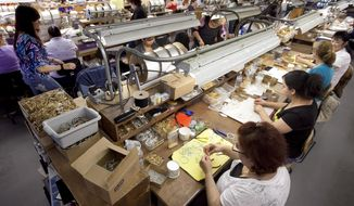"""FILE - In this July 26, 2012 file photo, workers at an Alex and Ani factory assemble jewelry in Cranston, R.I. The company maker filed a discrimination lawsuit in July 2019 in federal court in New York that alleges """"gender bias and greed"""" by Bank of America has led to a financial """"death spiral"""" at the company. The lawsuit says bank """"wants the women out of power at Alex and Ani."""" The company was founded by Carolyn Rafaelian in 2004, and was selected by the U.S. Olympic Committee to produce the charms for the 2012 London Games. (AP Photo/Steven Senne, File)"""
