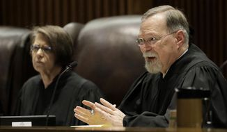 FILE - In this May 9, 2019, file photo, Kansas Supreme Court Chief Justice Lawton Nuss, right, asks a question while Justice Marla Luckert listens during oral arguments in a school funding case in Topeka, Kan. Nuss plans to retire in December, giving Democratic Gov. Laura Kelly a second appointment on the court. Nuss announced Friday, July 26, 2019, that he plans to step down Dec. 17 after serving on the court since 2002 and as chief justice since 2010. He was an appointee of moderate Republican Gov. Bill Graves.(AP Photo/Charlie Riedel, File)