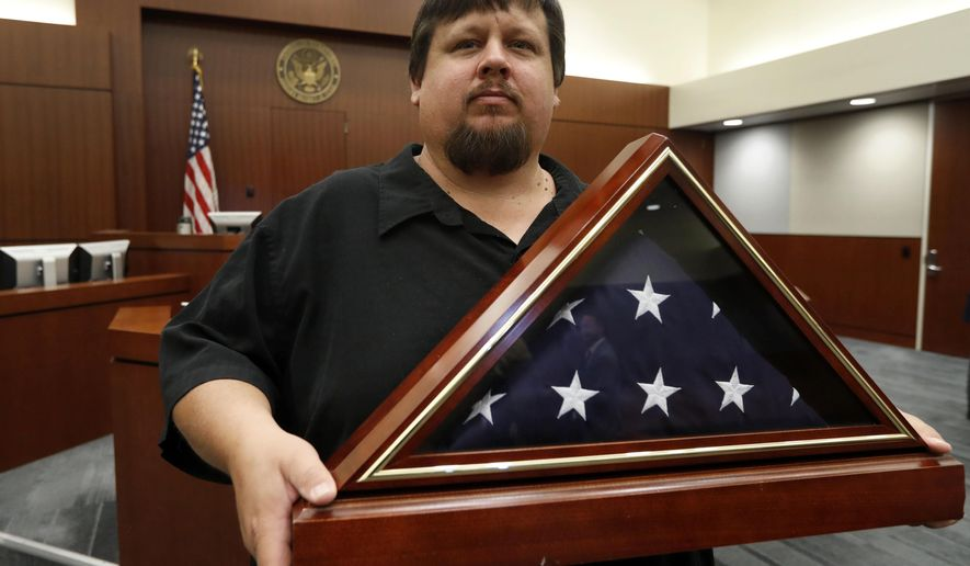 """Gary Hulsey, a 40-year-old resident of Wylie, Texas, holds a folded flag that was presented to him at the United States Courthouse in Plano, Texas, Friday, July 26, 2019. Judges and senior officials with the U.S. Marshals Service gathered at the North Texas courthouse to present the flag to the great, great, great grandson of Marshal Russell Wireman, who was shot in the chest in 1889 during the so-called """"Moonshine War."""" (AP Photo/Tony Gutierrez)"""