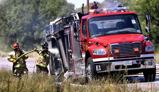 In this Thursday, July 25, 2019 photo, Abilene firefighters hose-down a Snyder Fire Department truck that caught fire on Westlake Road as it was being driven to a maintenance shop in Abilene, Texas. (Ronald W. Erdrich/The Abilene Reporter-News via AP)
