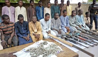 FILE- In this Wednesday July.18, 2018 file photo, A group of men identified by Nigerian police as Boko Haram extremist fighters and leaders are shown to the media, in Maiduguri, Nigeria. Suicide bombings, mass kidnappings, tens of thousands of people killed. A ghastly insurgency by the homegrown Islamic extremist group Boko Haram marks 10 years this week in northeastern Nigeria, where many residents say life has been set back by decades. (AP Photo/Jossy Ola, File)