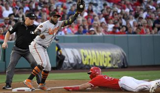 Los Angeles Angels' Mike Trout, right, dives safely into third on a wild pitch as Baltimore Orioles third baseman Hanser Alberto takes a late throw during the first inning of a baseball game, Thursday, July 25, 2019, in Anaheim, Calif. (AP Photo/Mark J. Terrill)