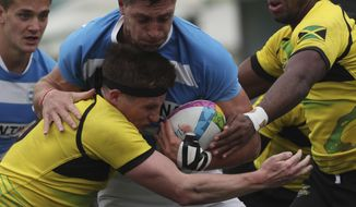 Matias Osadczuk of Argentina, center, is tackled by Rhodri Adamson of Jamaica, left, during rugby seven match at the Pan Am Games in Lima, Peru, Friday, July 26, 2019. Argentina won the match 52-0. (AP Photo/Juan Karita)