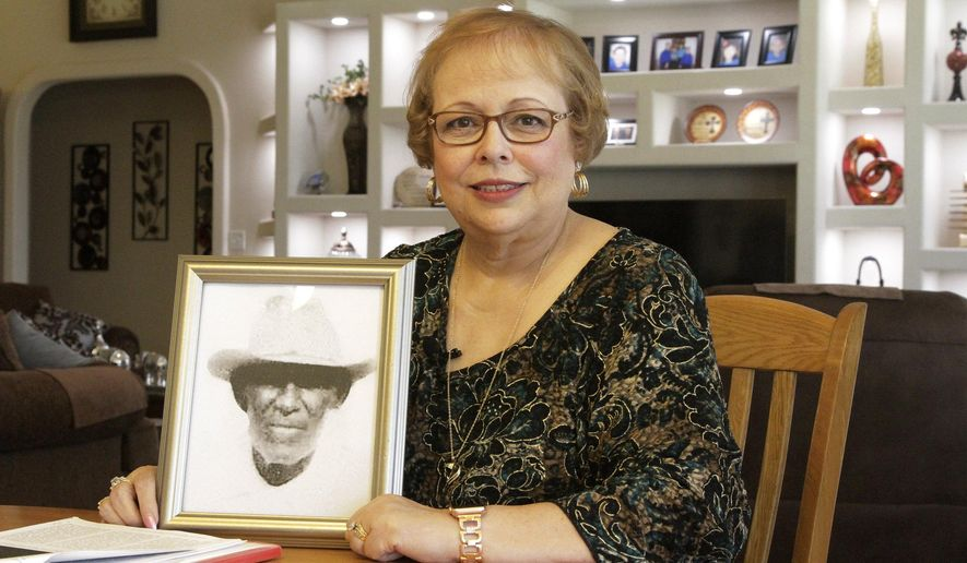 "In this April 30, 2019, photo, Arlinda Valencia poses at her home in El Paso, Texas, with a portrait of her great-grandfather Longino Flores, who was murdered at the age of 44 by Texas Rangers and U.S. Army soldiers in the Porvenir Massacre of 1918. As the U.S. prepares to remember the 100th anniversary of ""Red Summer,"" a period in 1919 when white mobs attacked and murdered African Americans in dozens of cities across the country, some historians and Latino activists say now also is the time to acknowledge the terror experienced by Mexican Americans right before that brutal year. (AP Photo/Cedar Attanasio)"