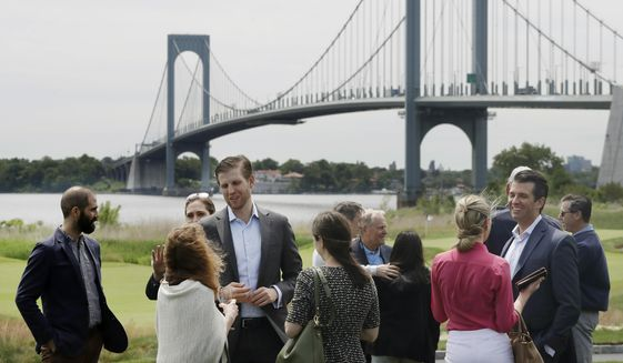 In this June 11, 2018 photo, President Donald Trump's sons, Eric Trump, third from left, and Donald Trump Jr., second from right, talk with guests at the opening of the Trump Golf Links clubhouse in the Bronx borough of New York. Behind them is the Whitestone Bridge. President Donald Trump's company posted annual losses at his golf course in the Bronx for the first time since it opened four years ago as expenses rose, greens fees barely budged and the opening of a clubhouse was delayed. (AP Photo/Mark Lennihan)