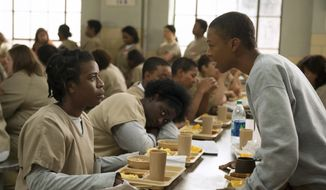 """FILE - In this file image released by Netflix, Uzo Aduba, left, and Samira Wiley appear in a scene from """"Orange is the New Black."""" The series' creative team said Thursday it has formed a fund that will support advocacy groups pressing for criminal justice reform and women re-entering society from prison, protect immigrants' rights and end mass incarceration. The fund, named in honor of show character Poussey Washington, will spread out every donation equally to eight already-existing nonprofit groups. The announcement comes on the eve of the Friday premiere of the series' seventh and final season. (Jojo Whilden/Netflix via AP, File)"""
