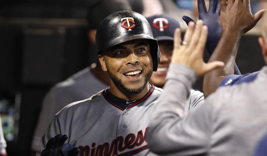 Minnesota Twins' Nelson Cruz celebrates with teammates in the dugout after hitting a solo home run during seventh inning of a baseball game against the Chicago White Sox, Friday, July 26, 2019, in Chicago. (AP Photo/Jeff Haynes)