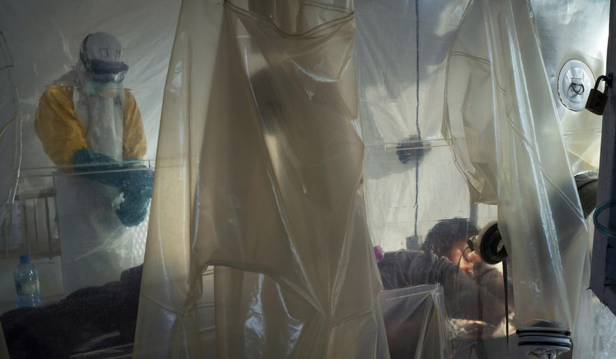 In this Saturday, July 13, 2019, file photo, health workers wearing protective gear check on a patient isolated in a plastic cube at an Ebola treatment center in Beni, Congo. On July 17, the World Health Organization declared the Ebola outbreak an international emergency after it spread to eastern Congo's biggest city, Goma. (AP Photo/Jerome Delay)