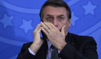 Brazil's President Jair Bolsonaro talks on his cell phone during a ceremony at Planalto presidential palace, in Brasilia, Brazil, Tuesday, July 23, 2019. (AP Photo/Eraldo Peres)